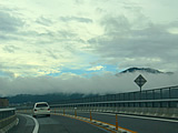 山の中腹に雲のベルトがかかり行く手には青空が見える四国路
